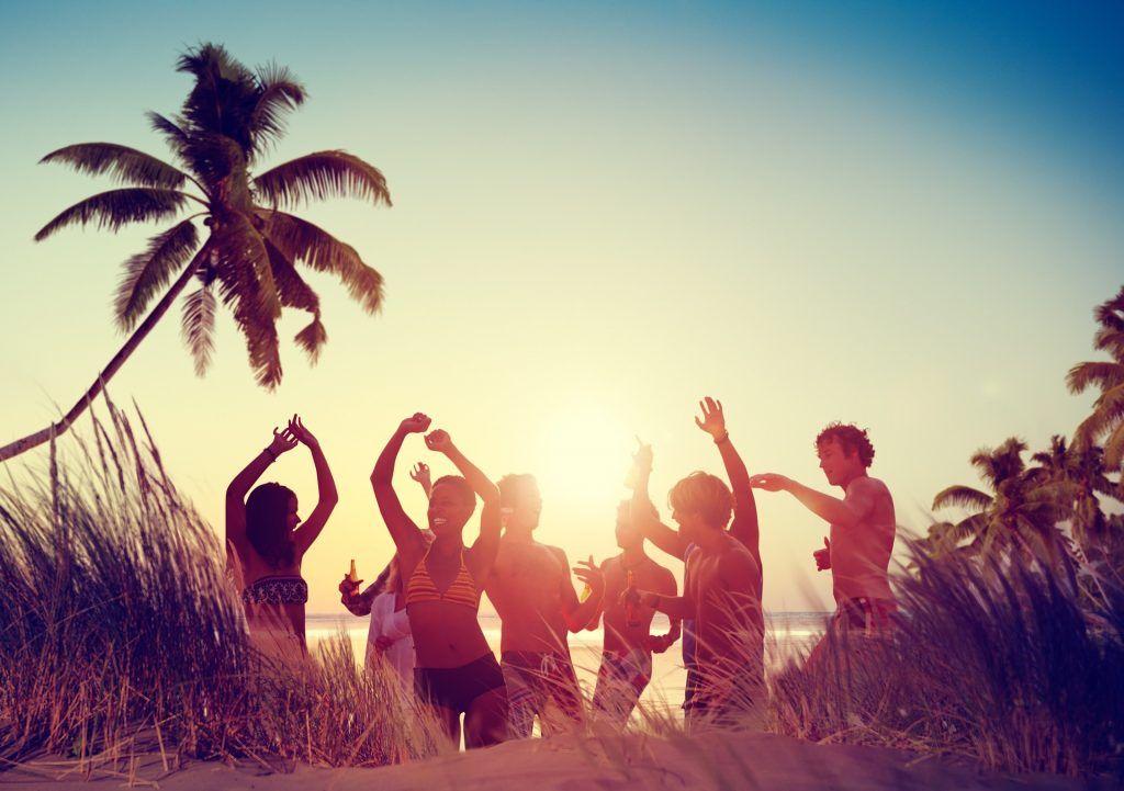Party von glücklichen, jungen Leuten am Strand