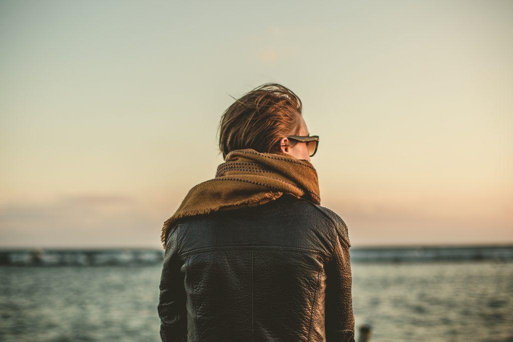 Mann blickt nachdenklich auf das Meer