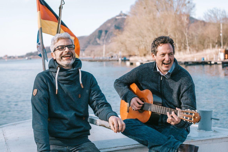 Eckart von Hirschhausen und Tobias Esch auf einem Boot, mit Gitarre